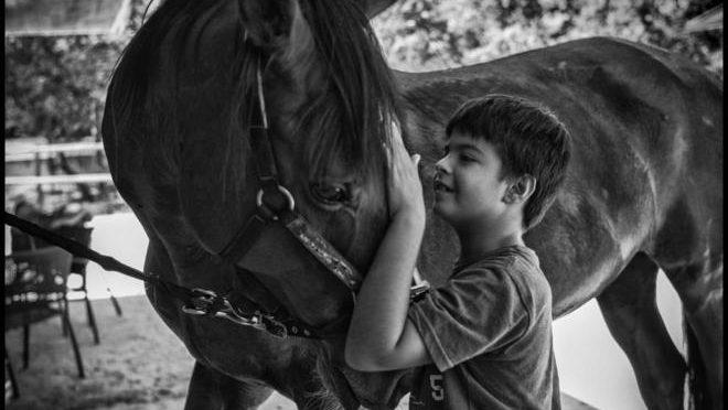 Liberto, con hiperactividad, cepilla a su caballo que le ayuda a relajarse.