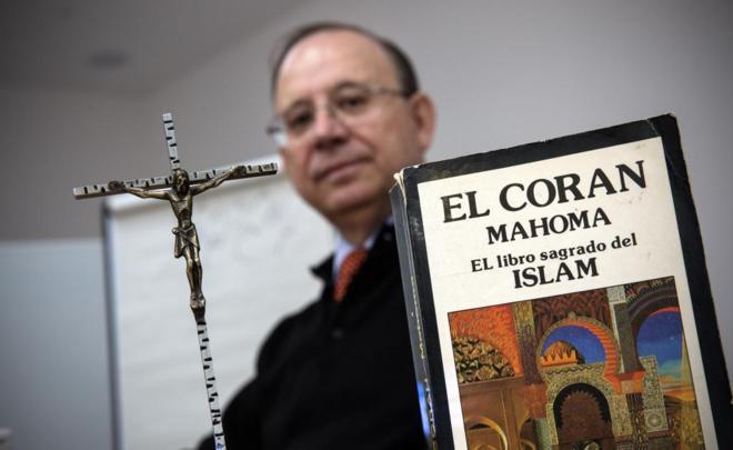 El cura diocesano José Luis Sánchez Nogales, con un crucifijo y el Corán