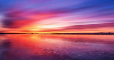Colores de atardecer violetas, amarillos, magentas, anaranjados, sobre el mar