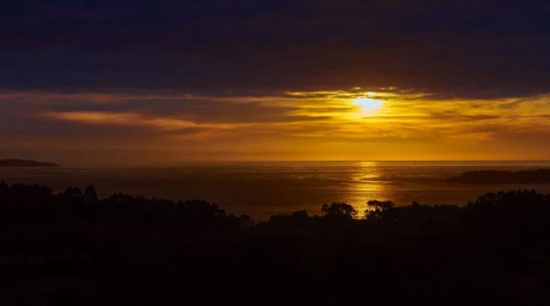 Atardece entre la costa y el horizonte