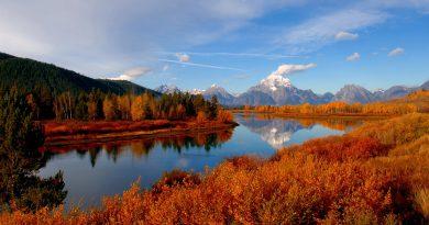Rio que atraviesa bosque de otoño. Montañas nevadas al fondo