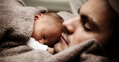 bebé arropado y recostado sobre su padre