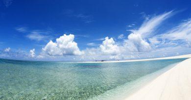 Playa con cielo azul y nubes de blanco intenso