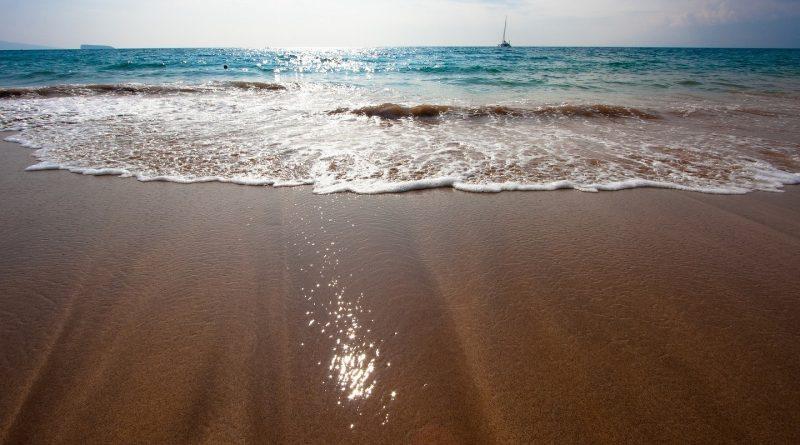 Velero en el horizonte se aproxima a la orilla