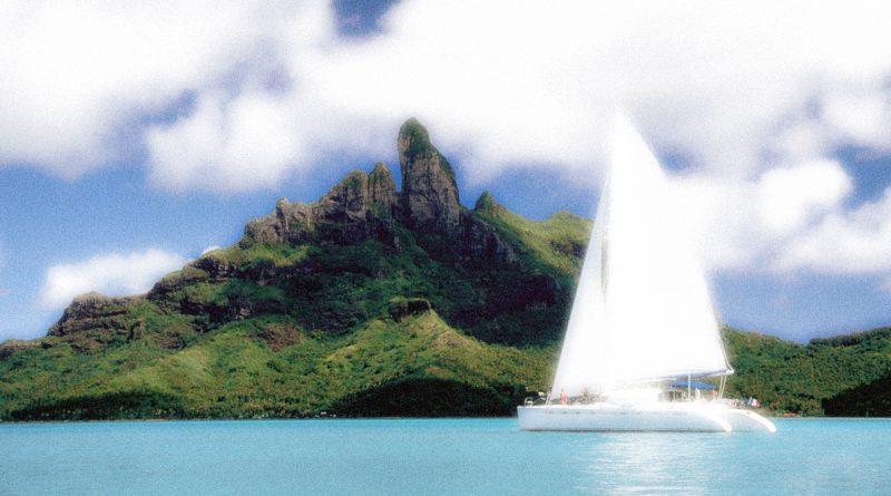 Catamarán frente a isla verde y montañosa
