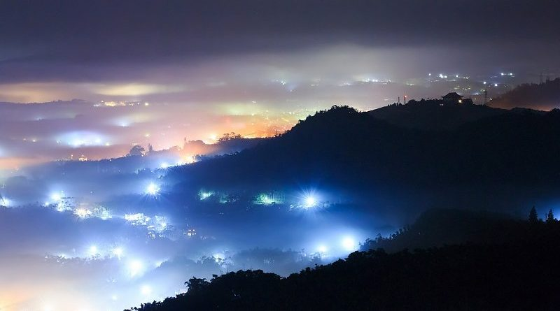 Ciudad iluminada entre la niebla, vista desde la montaña