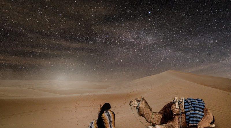 Desierto, hombre de pelo largo bajo una túnica y camello, ambos sentados sobre la arena del desierto bajo la noche estrellada (Fuente: pixabay - autora: Myriam Zilles)