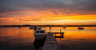 Lancha atracada en el muelle del lago, a la puesta de sol
