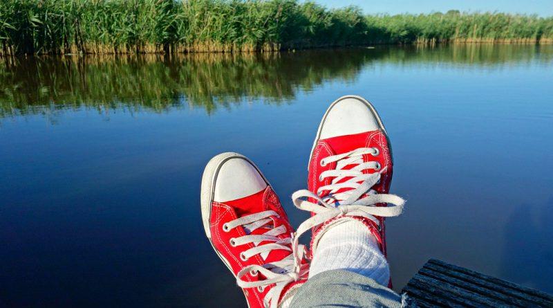 Zapatillas rojas. Pies cruzados contemplando los juncos sobre el agua