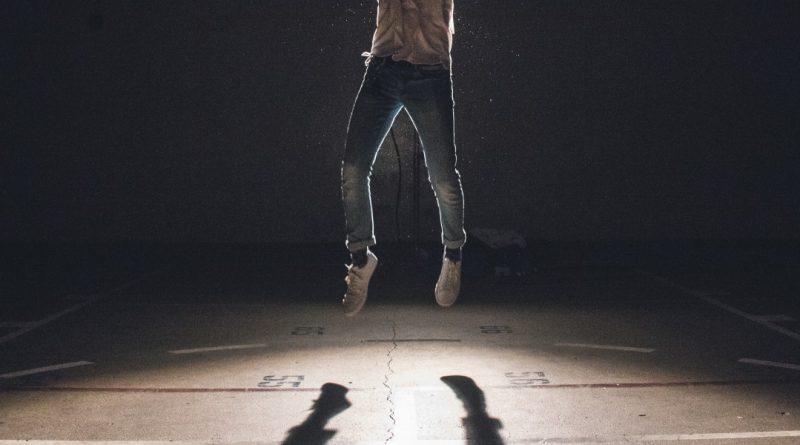 hombre saltando (sólo se ve de cintura hacia abajo. Sombra de sus pies proyectada en el suelo).
