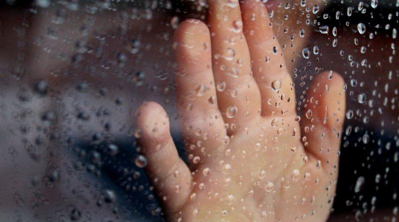 Mano apoyada en el cristal mojado por la lluvia