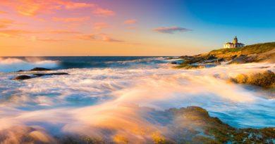 Mar rompiendo sobre el faro de la costa, al amanecer