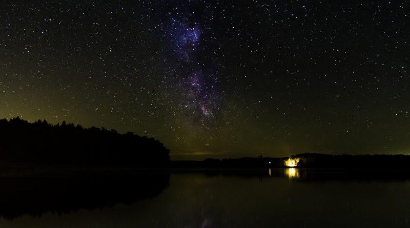 Luz de campaña frente a la Vía Láctea