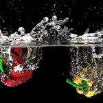 Chapoteando en colores. Dos pimientos (uno rojo y otro amarillo) que caen sobre el agua y se sumergen, salpicando