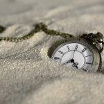 Reloj de mano semienterrado en la arena (Fuente: Pixabay.com - annca)