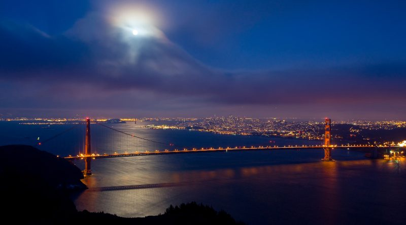 Puente colgante, ciudad iluminada, de noche