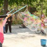 En El Retiro de Madrid: Niña haciendo pompas inmensas de jabón ayudado por un adulto