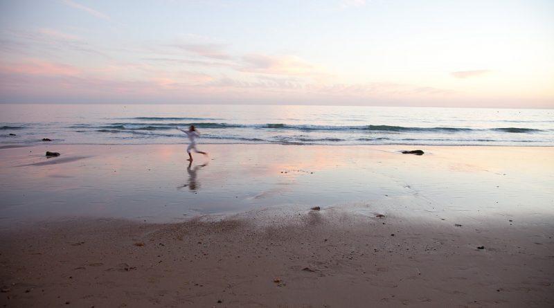 Niño corriendo por la playa mojada en olas cuando cada el atardecer y se ven los brillos sobre la arena húmeda